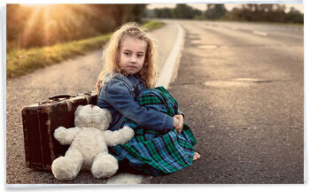Young girl sitting beside the road with suitcase and teddy waiting